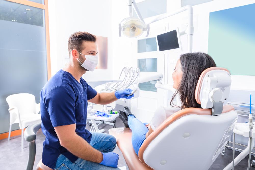 młody dentysta wykonuje zabieg pacjentce