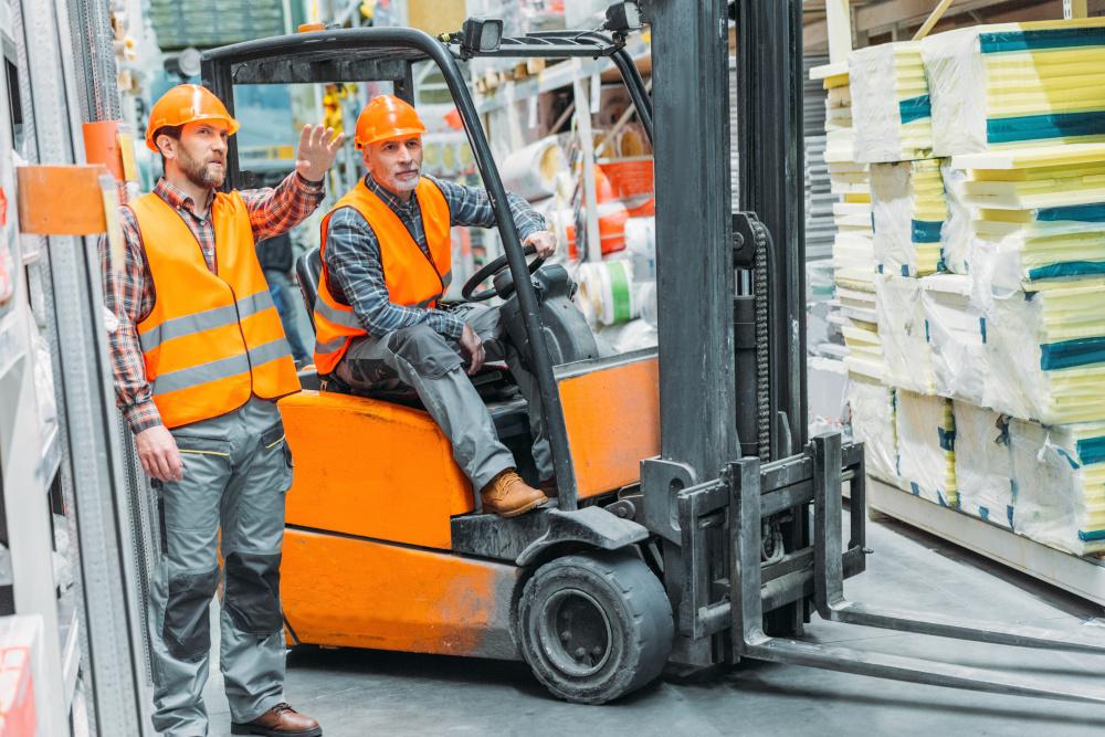 pracownik siedzący na wózku widłowym i przewożący materiały oraz starszy pracownik rozmawiający z pracownikiem na wózku