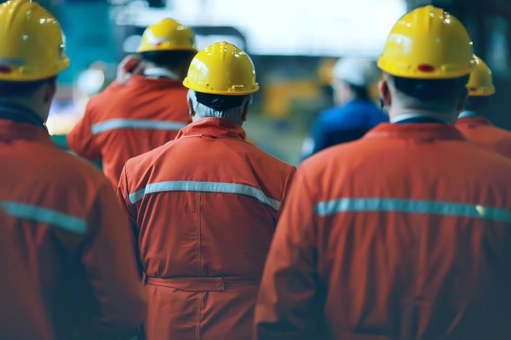 pracownicy w strojach ochronnych i kaskach ustawieni tyłem