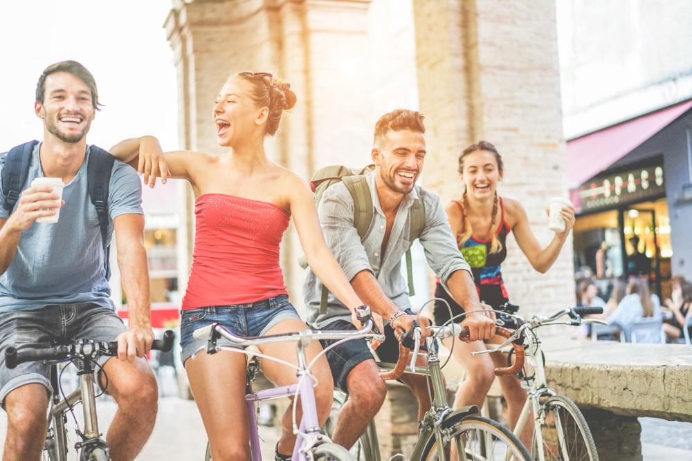 Grupa szczęsliwych przyjaciół jeżdżąca na rowerach